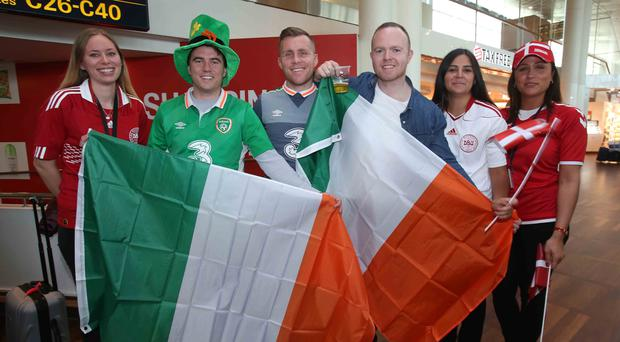 Republic of Ireland fans are greeted by Danish members of staff, wearing their national colours, as they arrive at Copenhagen Airport ahead of the FIFA World Cup qualifying play-off first leg match between Denmark and the Republic of Ireland