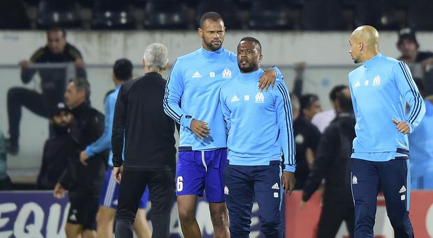 Marseille's Patrice Evra, center right, is led away by his teammate after an incident with Marseille supporters