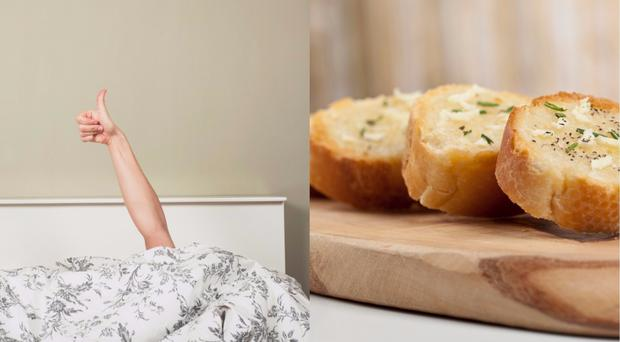 Someone in bed and garlic bread
