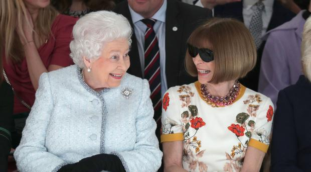 Queen Elizabeth II sits next to Anna Wintour as they view Richard Quinn's runway show (Yui Mok/PA)