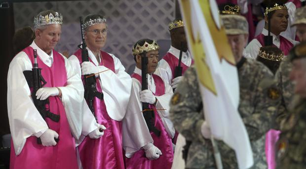 Men wear crowns and hold unloaded weapons at the World Peace and Unification Sanctuary, in Newfoundland, Pennsylvania (Jacqueline Larma/AP)