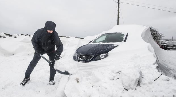 Adam Suthers digs out a car stuck in the snow in Ripponden