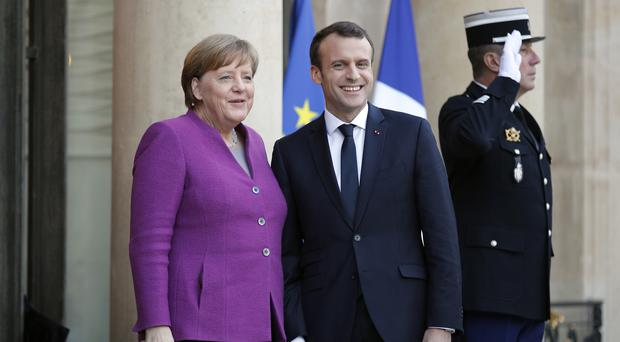 The German and French leaders were seen warmly embracing (Francois Mori/AP)
