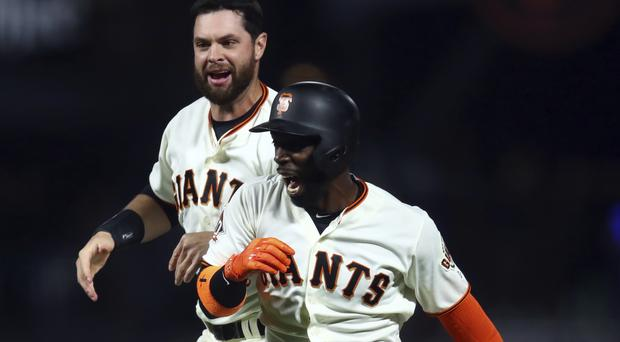 San Francisco Giants' Andrew McCutchen, right, celebrates with Brandon Belt