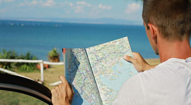 A man stands near a car looking at a road map