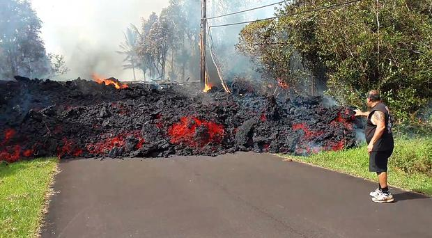 A man looking at the lava flow in Hawaii