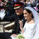 Prince Harry and Meghan wave to the crowds (Kirsty O'Connor/PA)