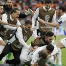 Uruguay footballers celebrate a goal against Egypt at the World Cup – (Natacha Pisarenko/AP)