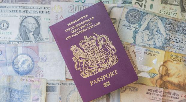 A British passport with oreign bank notes (Anthony Devlin/PA)