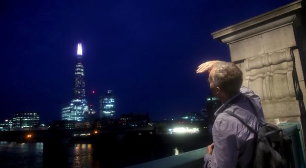 "A man looks for the ""Blood moon"" as clouds over the London skyline obscure the view (Yui Mok/PA)"