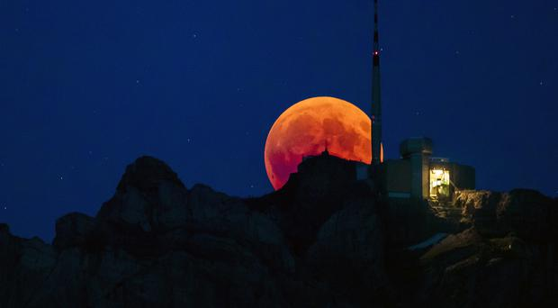 The moon turns red during a total lunar eclipse in Switzerland – (Christian Merz/AP)