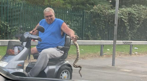 A man on a mobility scooter holding a snake was photographed in south London (David Videcette/PA)