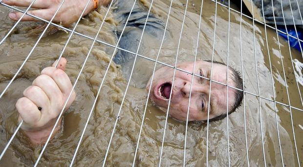 Racers go through freezing cold water on a Tough Mudder course (PA)