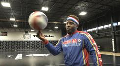 Harlem Globetrotter Too Tall Hall spins a basketball on his finger – (PA)