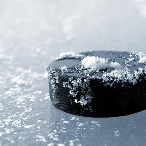 A hockey puck lying on an ice rink – (vencavolrab/Getty Images)