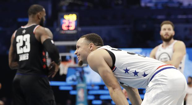 Team Giannis' Stephen Curry, of the Milwaukee Bucks smiles on the court as Team LeBron's LeBron James, of the Cleveland Cavaliers, looks on during the first half of an NBA All-Star basketball game, Sunday, Feb. 17, 2019, in Charlotte, N.C. (AP Photo/Chuck Burton)