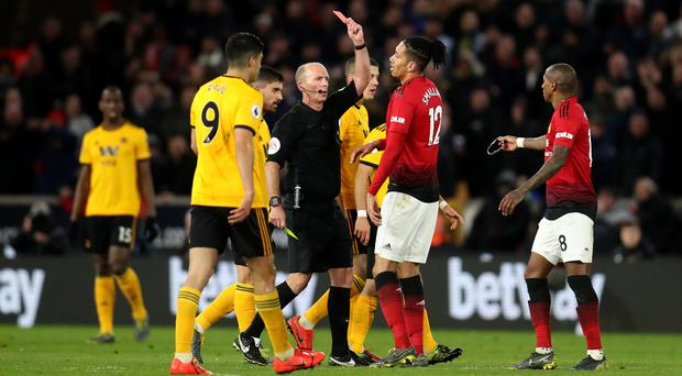 Match referee Mike Dean shows a red card and sends off Manchester United's Ashley Young during the Premier League match at Molineux Stadium, Wolverhampton (PA)