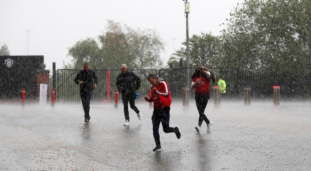 Manchester United fans race to the ground in the heavy rain before the Premier League match at Old Trafford (Martin Rickett/PA)
