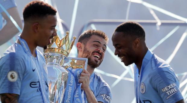 Manchester City's Bernardo Silva holds the English Premier League trophy after the English Premier League soccer match between Brighton and Manchester City at the AMEX Stadium in Brighton (Frank Augstein/AP)
