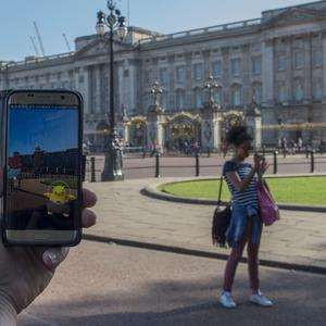 People playing the Pokemon Go reality game on their phone outside Buckingham Palace in London (PA)
