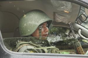 A heavily militarised police officer sits in a car, wearing a hat and holding a rifle
