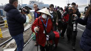 A passenger is surrounded by the media after disembarking from the quarantined Diamond Princess cruise ship in Yokohama, near Tokyo (Jae C Hong/AP)