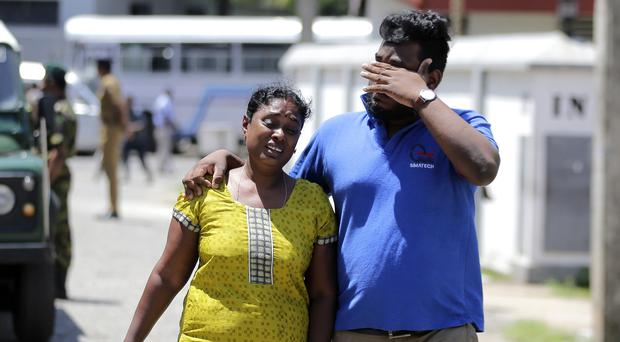 A Sri Lankan couple mourns after identifying a body in Colombo (Eranga Jayawardena/AP)