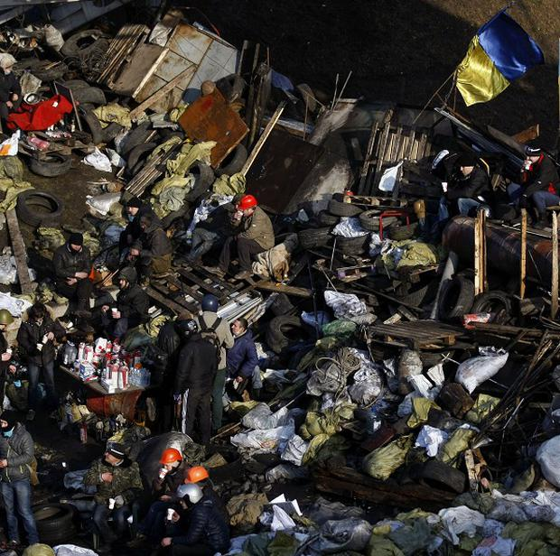 Anti-government protesters man a barricade at Independence Square in Kiev, Ukraine (AP)