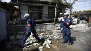 Police officers search for people possibly trapped at a damaged home in Mashiki (AP)
