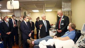 Vice President Mike Pence, without a face mask, meets patient Dennis Nelson, right, who survived the coronavirus, during Mr Pence's visit to the Mayo Clinic (Jim Mone/AP)