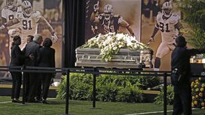 Fans view the casket of former Saints star Will Smith during a public viewing inside the Saints training facility in Metairie