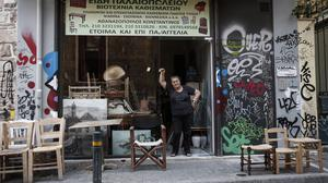 Business owner Katherina Athanasopoulou poses at the entrance of her workshop in central Athens as bailout talks continue (AP)