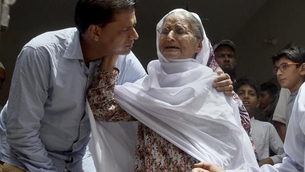 Abdul Aziz Sheikh comforts an elderly woman upon the news his daughter has died in a US school shooting (Fareed Khan/AP)