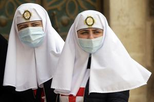 Two nuns wear protective face masks at the Church of the Holy Sepulchre (Mahmoud Illean/AP)