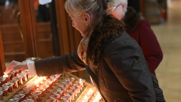 A woman lights a candle