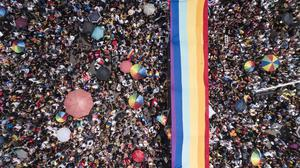 Revellers unfurl a rainbow flag during the parade in Mexico City (AP Photo/Christian Palma)