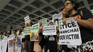 A migrant workers alliance group holds placards to protest against the killings of the two women outside the High Court in Hong Kong (AP)