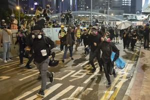 Protesters run as riot police charge from behind during a rally at Edinburgh Place in Hong Kong (Vincent Thian/AP)
