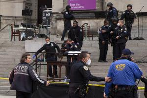 New York police officers carry a suspected gunman on a stretcher down the steps of the cathedral (Ted Shaffrey/AP)