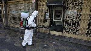 A firefighter disinfects an ATM machine in Iran (Vahid Salemi/AP)