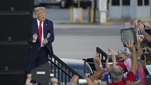 President Donald Trump greets supporters as he arrives at a campaign rally at the Orlando Sanford International Airport on Monday (John Raoux/AP)