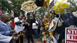 A trumpeter plays in front of a makeshift memorial as people march in honour of Saints stars Will Smith