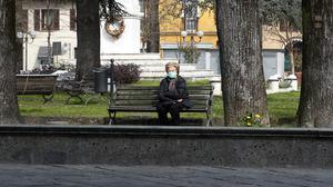 An elderly woman sits on a bench in Codogno, Italy (Antonio Calanni/AP)