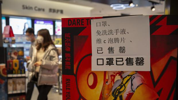 People walk past a sign at a drug store saying that it is sold out of face masks in Beijing (AP/Mark Schiefelbein)