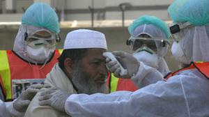 Pakistani health personnel take part in a drill as a preventative measures during an emergency of coronavirus outbreak, in Peshawar Pakistan, Monday, March 3, 2020. Pakistani health officials reported coronavirus cases in Pakistan. (AP Photo/Muhammad Sajjad)