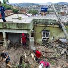 Local people work to clean up mud and debris around houses destroyed by a landslide after heavy rains in Vila Ideal area of Ibirite municipality, Minas Gerias state (AP)