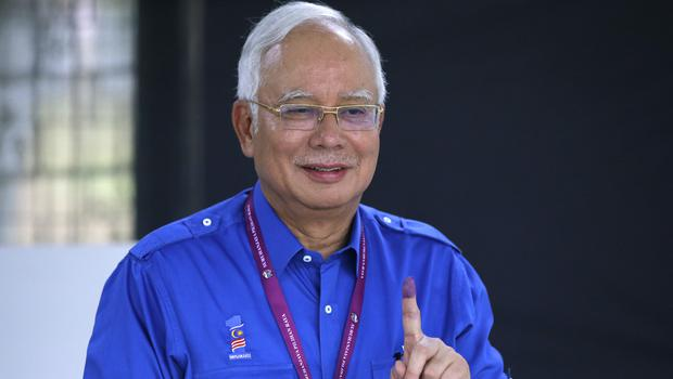 Malaysian PM Najib Razak shows his finger marked with ink after voting at his hometown in Pekan (Aaron Favila/AP)