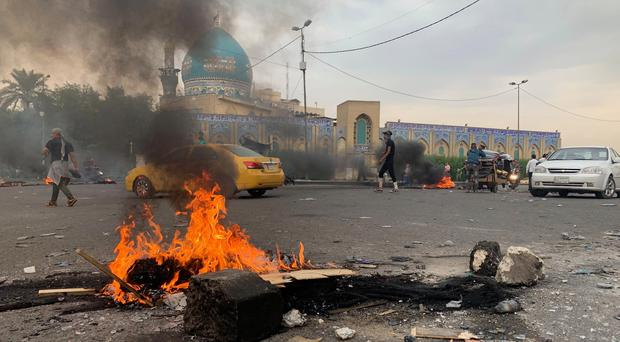 Protesters set a fire near the Khilani Mosque during ongoing anti-government protests in Baghdad (Ali Abdul Hassan/AP)