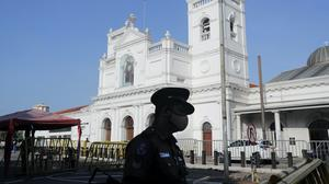 A Sri Lankan police officer stands guard outside St Anthony's church, one of the sites of the 2019 Easter Sunday attacks (Eranga Jayawardena/AP)