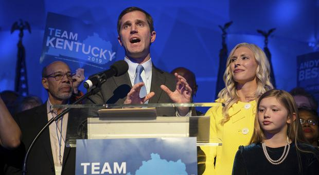 Andy Beshear stands with his wife, Britainy, as he delivers a speech (Bryan Woolston/AP)